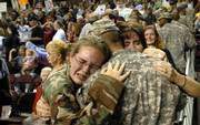 Staff Sgt. Alexander Parker, Berryton, Kan. receives a heartfelt welcome from his daughter Page, 11, and wife Daisy as soldiers hurry to find their loved ones following a homecoming ceremony for the Kansas National Guard's 2nd Battalion, 137th Infantry, after returning from service in Iraq, Thursday afternoon at the Kansas Expocentre. About 450 soldiers were welcomed home by family and friends.