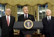 President Bush, center, is flanked by outgoing Defense Secretary Donald H. Rumsfeld, left, and his replacement nominee Robert Gates. Bush announced Wednesday that Rumsfeld would be leaving the post he had held for six years.