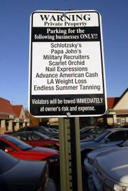 A parking sign warns drivers where to park for specific stores at Louisiana Purchase, a shopping center at 23rd and Louisiana streets.  Several shoppers have had their vehicles towed from the parking lot.
