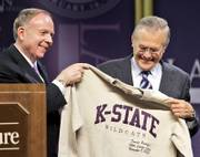 Kansas State University President Jon Wefald, left, presents Defense Secretary Donald Rumsfeld with a shirt after his Landon Lecture Thursday in Manhattan. Rumsfeld spoke a day after resigning.