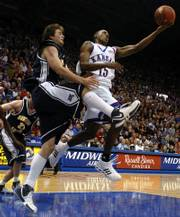 Kansas guard Mario Chalmers flips extends for a shot behind the back over Northern Arizona forward Kyle Landry during the second half of Saturday night's game against the Lumberjacks at Allen Fieldhouse.