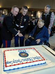 KU ROTC Marine Officer Instructor Major Jeff Daniels, from left, and ROTC Cadet Jordan Alley cut a cake with a sword as Charles Laskowski Sr. and his son, Charles Laskowski Jr., look on from right. At 90 years old, Laskowski Sr. was the oldest Marine in attendance, and Alley, 20, was the youngest. Both were recognized at a birthday party for the Marine Corps on Friday at the Dole Institute of Politics.