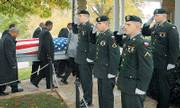 """Fort Leavenworth honor guard members, from center, Pfc. Jon Westall, Pfc. David Tulette, Pvt. Sven Johnson and Pvt. Derek Stephansen-Fitzgerald salute as pall bearers for World War II veteran Leon Holmes, who died Oct. 17, make their way into the Committal Shelter on Oct. 25 at Fort Leavenworth National Cemetery. The honor guard appears at funerals of veterans and also """"present the colors"""" at sports venues and other events."""