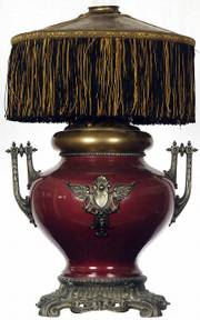 This 19th-century kerosene lamp has a metal urn with cast-iron base and trim. The leather shade has fringe hanging from the sides. Notice the hole in the top of the shade to accommodate the heat and flame of the burning kerosene. It sold at a Woody Auction in Douglass this fall.