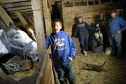 Jeffery Kirk, 11, left, helps his family finish some evening chores by feeding their horses. In the background are, from left, Jeffery's mother, Anne; his brother, Steven, 8; and his father, Paul Kirk. The Kirks think they have a good life but, like other middle-class families nationwide, have watched as  factors like rising fuel and health care costs have managed to put them in a tighter financial squeeze. The Kirks live in rural Douglas County where the median family income is $57,572, with Lawrence just short of that at $55,537, according to the U.S. Census American Fact Finder.