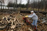 Bill Foust, property manager at Spirit Lake, a retreat center in southern Jefferson County, adds to his wood pile Tuesday afternoon while using a gas-powered splitter. Foust spent part of the day splitting the wood which he plans to sell and deliver this winter.