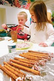 PETE JUNGE, left, and Parrish Mock make pretzel sticks in their preschool class at the Lawrence Arts Center, 940 N.H., in this December 2005 file photo. The project was for the Children's Holiday Shop, an annual event that will be Dec. 9. The arts center has numerous activities for kids during the holiday season.