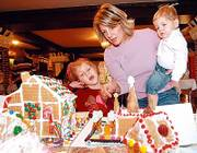 Parker Weber, left, her mother, Amy Weber, Lawrence, and her 18-month-old brother, Brady Weber, view entries two days before the 2005 Big Brothers/Big Sisters Gingerbread House Auction. This year's event begins Saturday at the Eldridge Hotel's Crystal Ballroom, 701 Mass.