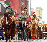 PARADE PARTICIPANTS greet spectators as they make their way down Massachusetts Street during the 2005 Old-Fashioned Christmas Parade. This is the 14th year for the annual event.