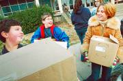 FROM LEFT, West Junior High School students Stefan Kuczera, Lucas Smith and Lilly Cottrell load some of the more than 500 canned food items that their seventh-grade class gathered in a food drive in this November 2005 file photo. Food pantries especially need nonperishable donations this time of year. Grocery store gift cards make good donations, too.