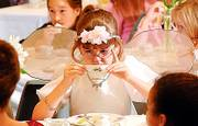 ADDIE SCHINKEL, 7, takes a sip of her drink during the Lawrence Public Library's annual Victorian Tea Party in this December 2005 file photo. This year's tea party will be Jan. 3.