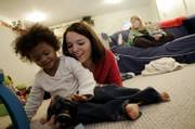 Jenna Hatfield, 25, plays Friday at her home in Cambridge, Ohio, with her 3-year-old biological daughter, Ariana, who was adopted by a Pennsylvania couple three years ago. Behind them, on the sofa, are Ariana's adoptive mother, Denise Loss, and Denise's 1-year-old son Joey.