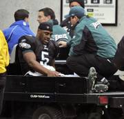 Philadelphia eagles quarterback donovan mCnabb holds his injured right knee as he is carted from the field against the Tennessee Titans. McNabb is out for the season because of the injury, suffered in the second quarter of Philadelphia's 31-13 loss to Tennessee on Sunday in Philadelphia.
