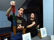 Robert Elder, left, and Jessica Finnearty use a colorful tube of Jell-O to symbolize different ages of rock layers during a biostratigraphy lesson during the Jell-O Nation event Sunday at the Kansas University Natural History Museum, put on by KU graduate students. Biostratigraphy is the idea of using fossils to determine the age of rock layers.