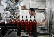 Mark Valenzano loads bottles of cranberry wine onto a labeling machine at Valenzano Winery in Shamong, N.J. Cranberries, although still a seasonal product, are turning up in places far removed from the Thanksgiving table.