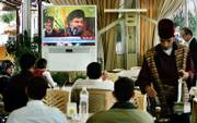 "A speech by Hezbollah leader Hassan Nasrallah is watched Sunday at a cafe in an amusement park in Beirut, Lebanon. Nasrallah urged his followers to be ""psychologically"" ready to take to the streets in mass demonstrations to support the militant group&squot;s demand for a national unity government."