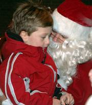 Joseph Schmidtberger,  of Lawrence, tells Santa Claus what he wants for Christmas last year at the Downtown holiday celebration. Santa will be back this year, arriving at 6 p.m. on the roof of Weaver's department store, Ninth and Massachusetts Streets.
