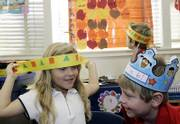 Nicole Super, 5, left, with Connor Apel, 6, right, and Andre Painter, 6, background, try on paper headbands for the annual Thanksgiving Day play put on by their kindergarten class at Kettering Elementary School in Long Beach, Calif. For years, students in this class have not been adding feathers to their American Indian headbands because they are considered sacred objects in American Indian cultures.