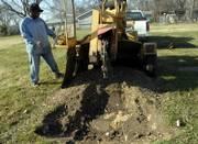 Frank Demby Jr., a Lawrence Parks and Recreation employee, operates a tree stump remover Wednesday in Memorial Park Cemetery. The city is planning to take over ownership of the cemetery on East 15th Street across from Oak Hill Cemetery. A judge has yet to rule on the ownership motion.