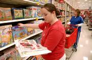 Amy Lewis, an employee in the toy department at SuperTarget, 3201 Iowa, checks a holiday advertising brochure against store stock in preparation for today's big shopping day. Lewis worked at the store on Wednesday.