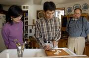 Kansas University graduate students from left, Xiaoting Cui, 29, and Xin Zhao 27, both from China, spent Thanksgiving Day at the home of John and Patricia Solbach. They helped prepare food for Thursday's holiday feast while learning about the American tradition.