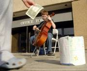 Alder Cromwell, 9, Lawrence, performs some classical music on his cello and earns some tips from passersby. Cromwell was downtown Friday where many people were out enjoying the nice weather and some holiday shopping.