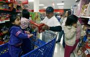 Ashley Miranda, 3, left, observes as her mother Leslie Marin, second from left, and a friend, Fernando Lucas, third from left, shop for toys during a Thanksgiving Day sale at Kmart in Los Angeles. Some stores aren't waiting for Black Friday to kick off the holiday shopping frenzy.