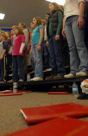 Folders containing choir music lay scattered on the floor as members of the Lawrence Children's Choir rehearse in this November 2005 file photo. The choir will give its fall concert on Saturday.