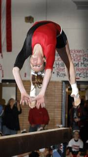 "LAWRENCE HIGH GYMNAST MALLORY WEST displays her talents for the crowd at ""Rock The House."" Monday night&squot;s event introduces the LHS winter sports teams to their fans, and helps the athletes prepare for playing in front of a crowd before this week&squot;s season openers."
