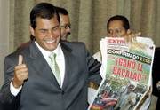"Ecuador&squot;s presidential candidate Rafael Correa smiles as he holds up a newspaper that reads ""The cod wins"" before a news conference in Guayaquil, Ecuador, on Monday. According to unofficial exit polls, Correa has a wide lead over Alvaro Noboa, a billionaire who is Ecuador&squot;s wealthiest man, after Sunday&squot;s runoff presidential elections."