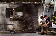 Anderson volunteer firefighters Adam Murphy, left, and Brandon Hines, rest on their truck after helping put out a fire at the Anderson Guest House, a group home for elderly and mentally ill, where 10 people died early Monday, Nov. 27, 2006, in Anderson Mo.
