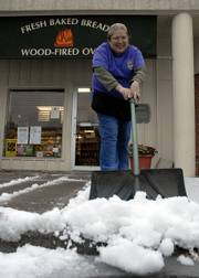 Jennie James, shift manager at Wheatfields Bakery, 904 Vermont, shovels off sleet outside the restaurant. A winter storm  Wednesday crossed over Lawrence dropping temperatures to below freezing