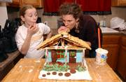 Jessica Brown and her Big Sister, Meg Hooper, snack as they finish their edible house in this 2006 file photo. Last year's Eldridge Gingerbread Festival & Auction raised $28,000, after expenses.