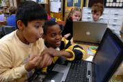 Cordley School second-graders Sam Allen, left, and Josh Bell play a video game at the end of class. Evondi Weston, second from right, and Ivan Greene, also played on a computer Wednesday. Cordley will celebrate its 90th birthday with a party Sunday at the school, 1837 Vt.