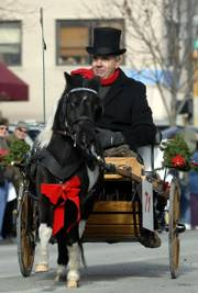 Jim Thomas, Oskaloosa, is pulled by a miniature horse in a two-wheel cart.