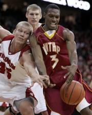 Wisconsin's joe krabbenhoft, left, reaches in on Winthrop's Mantoris Robinson. No. 11 Wisconsin survived a scare Monday, defeating Winthrop, 82-79 in overtime, in Madison, Wis.