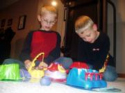 K.J. Lashley, 9, left, plays a board game with his brother Jacob, 6, on Friday night at their home in southeastern Lawrence. On Friday morning, K.J., a St. John Catholic School third-grader, donated money that would have covered the cost of his own birthday presents to the Boys and Girls Club of Lawrence.