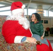 Jerred Willits, 2, tells Santa what he wants for Christmas on Saturday at the Toys for Tots drive at the Dole Institute of Politics.