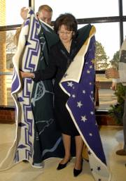 Karen Swisher, president of Haskell Indian Nations University, accepts a blanket on behalf of the Board of Regents from Regent Paul Ninham. The gift was part of a farewell reception for Swisher, who is retiring after seven years as president.