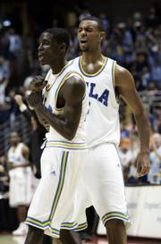 UCLA's Darren Collison, left, celebrates his buzzer-beating three-pointer at the end of the first half. Collison led UCLA to a 65-62 victory against Texas A&M on Saturday in Anaheim, Calif.