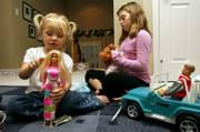 "Aidia Bryant, 3, left, and her sister Cassidy Moock, 10, play with their Barbie dolls in Lorton, Va. ""Barbies are awesome,"" says Cassidy. ""They&squot;re like little people you get to dress yourself."" Nearly 50 years after Mattel introduced Barbie, she has managed to thrive, especially in a time when classic toy makers have found themselves scrambling to attract new audiences."