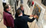 Land owners Mike Koehler and his son Dan Koehler talk to KDOT representative Kris Norton during the South Lawrence Trafficway open house held at the National Guard Armory. The Koehlers favor the 32nd Street route. They own 6.5 acres south of the Wakarusa.