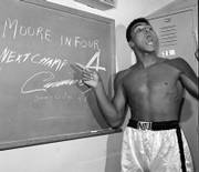 "A young Muhammad Ali points to a sign he wrote in his dressing room before his fight against Archie Moore in Los Angeles, in this Nov. 15, 1962, file photo predicting he&squot;d knock Moore out in the fourth round, which he did. The sign also predicts Ali will be the next champ via a knockout over Sonny Liston in eight rounds. ""Ali Rap: Muhammad Ali the First Heavyweight Champion of Rap,"" proclaims Ali&squot;s verbal barrage was the beginning of hip-hop."