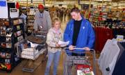 Kansas Jayhawk freshman guard Brady Morningstar shops shops for a Salvation Army family with the help of his mother at Wal-Mart. Each member of the basketball team could spend $100 to shop for a Salvation Army family Sunday night.