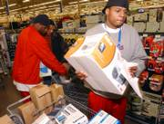Kansas Jayhawk sophomore guard Brandon Rush picks out a CD player as Darnell Jackson and Ronnie Chalmers, director of basketball operations, also shop for Salvation Army families at Wal-Mart. Each member of the basketball team could spend $100 to shop for a Salvation Army family.