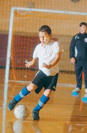 Robert Kleibohmer, 7, practices dribbling in and out of cones during an indoor soccer clinic at the East Lawrence Recreation Center.