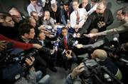New York Knicks coach Isiah Thomas, center, is surrounded by reporters asking him about the suspensions handed down by the NBA for the Knicks and Nuggets. The teams brawled Saturday in New York, and Commissioner David Stern meted out his punishments Monday.