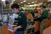 Hastings guest service associate Ian Mack, of Lawrence, carries a stack of buyback CDs and DVDs Wednesday afternoon at the 23rd Street store. Many shoppers sell their used items to receive extra holiday cash this time of year.