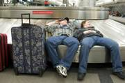 John, left, and Summer Cox, of Wilmington, Ill., rest on a Denver International Airport baggage carousel while they wait out the storm that closed the airport.