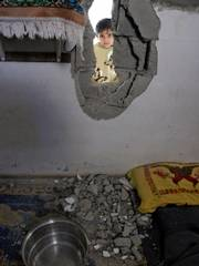 Jenin Al-Masri looks into her family's house in the northern Gaza Strip town of Beit Hanoun. A Palestinian rocket aimed at Israel veered off course and struck the home Thursday, wounding a 2-year-old boy sleeping in his bedroom, hospital officials and residents said.